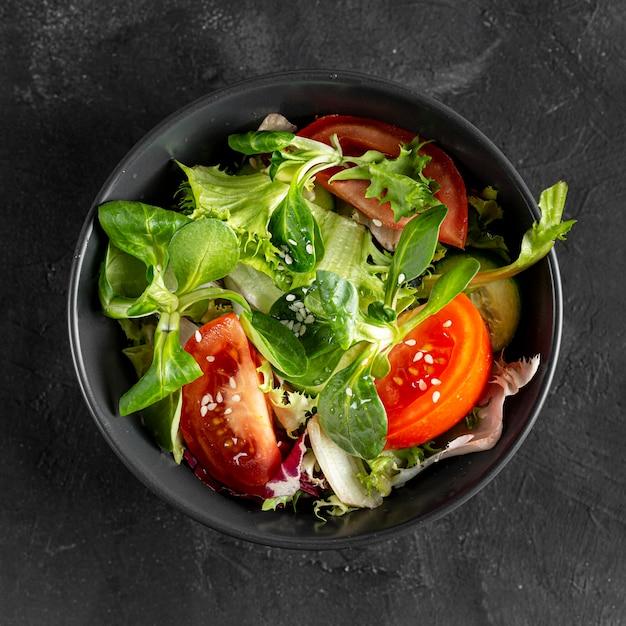 Bovenaanzicht salade in donkere kom Gratis Foto