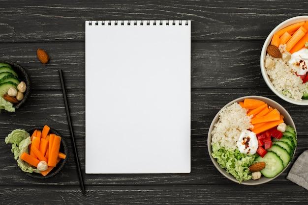 Bovenaanzicht salade met couscous en blanco blocnote Gratis Foto