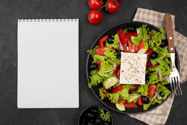 Bovenaanzicht salade met fetakaas en tomaten met leeg notitieboekje Gratis Foto