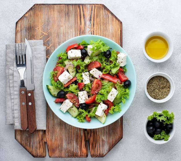 Bovenaanzicht salade met fetakaas op snijplank met olijven Gratis Foto