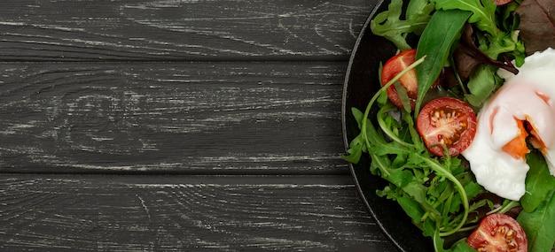 Bovenaanzicht salade met gebakken ei en kopie-ruimte Gratis Foto