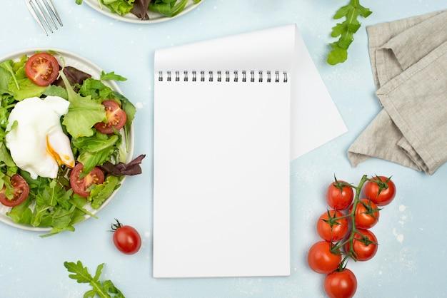 Bovenaanzicht salade met gebakken ei en tomaten met lege blocnote Gratis Foto