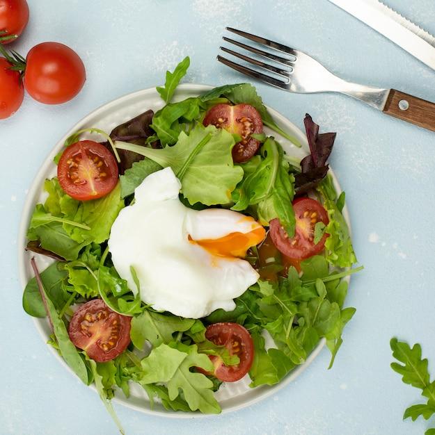 Bovenaanzicht salade met gebakken ei en tomaten Gratis Foto