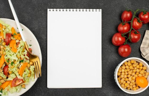 Bovenaanzicht salade met kikkererwten en tomaten met lege blocnote Gratis Foto