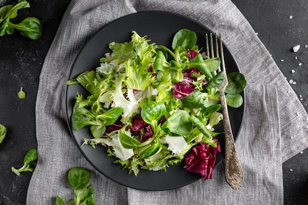 Bovenaanzicht salade met verschillende ingrediënten op een donkere plaat Gratis Foto