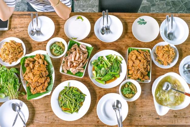 Bovenaanzicht schot; thais lokaal voedsel stond op de houten tafel en de aziatische vrouw stond klaar om te eten. Premium Foto