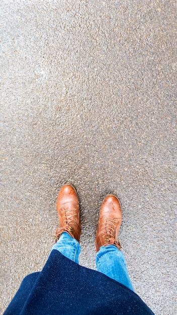 Bovenaanzicht selfie van vrouw voeten in bruine herfst laarzen op een nat asfalt na regen. Premium Foto