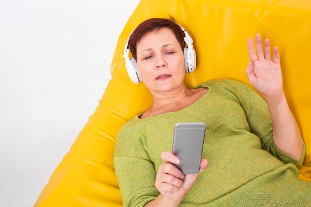 Bovenaanzicht senior vrouwelijke luisteren muziek Gratis Foto