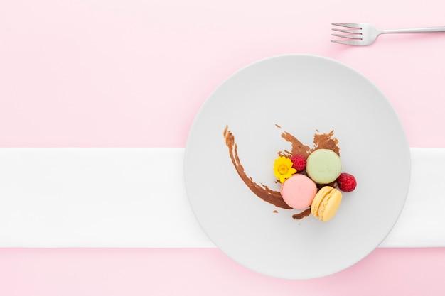 Bovenaanzicht smakelijke macarons op een bord Gratis Foto
