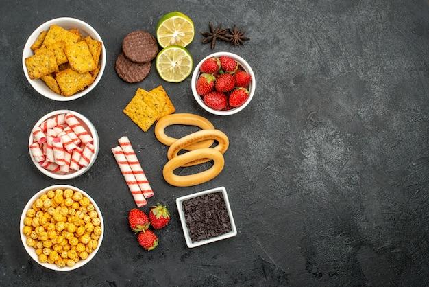 Bovenaanzicht smakelijke snacks met crakers limoen en sappige aardbeien cacaobloem kerstmissuikergoed op een donkere achtergrond met vrije ruimte Gratis Foto