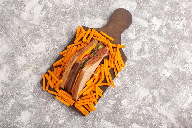 Bovenaanzicht smakelijke toast sandwich met kaas ham samen met frietjes op de witte achtergrond sandwich eten maaltijd Gratis Foto
