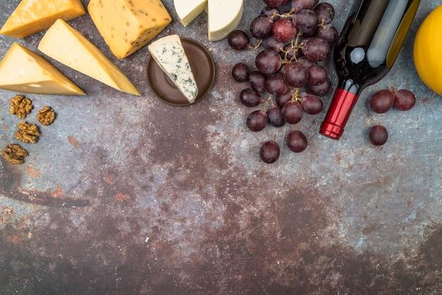 Bovenaanzicht smakelijke verscheidenheid aan kaas met druiven en fles wijn Gratis Foto