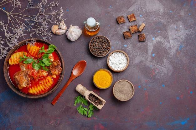 Bovenaanzicht smakelijke vleessaus met verschillende kruiden op zwart Gratis Foto