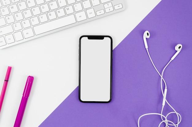 Bovenaanzicht smartphonemalplaatje over werkruimte Gratis Foto