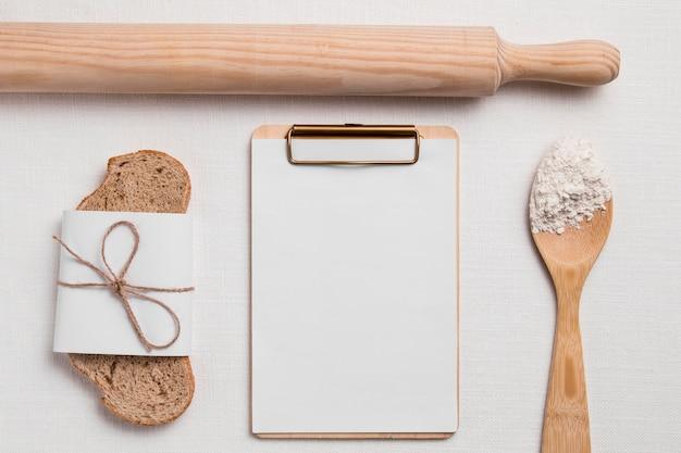 Bovenaanzicht sneetje brood met leeg klembord en deegroller Gratis Foto
