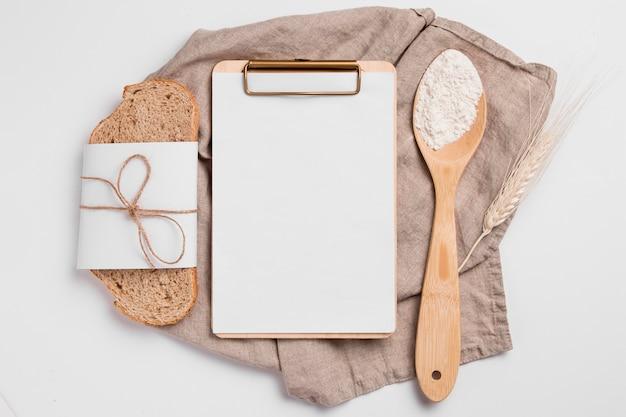 Bovenaanzicht sneetje brood met leeg klembord en houten lepel Premium Foto