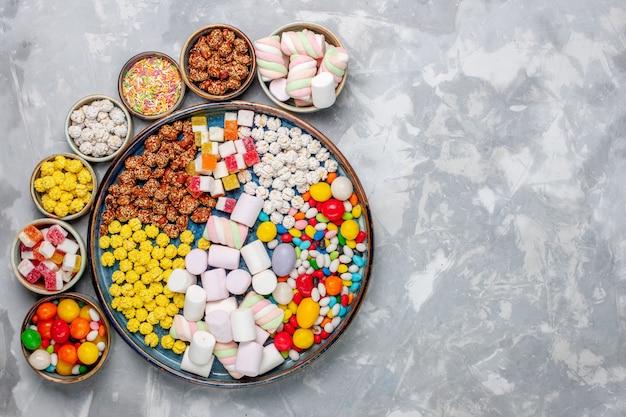 Bovenaanzicht snoep samenstelling verschillende gekleurde snoepjes met marshmallow in potten op lichte witte bureausuikergoed bonbon zoete confiture Gratis Foto
