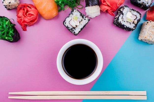 Bovenaanzicht sojasaus en sushi broodjes Gratis Foto