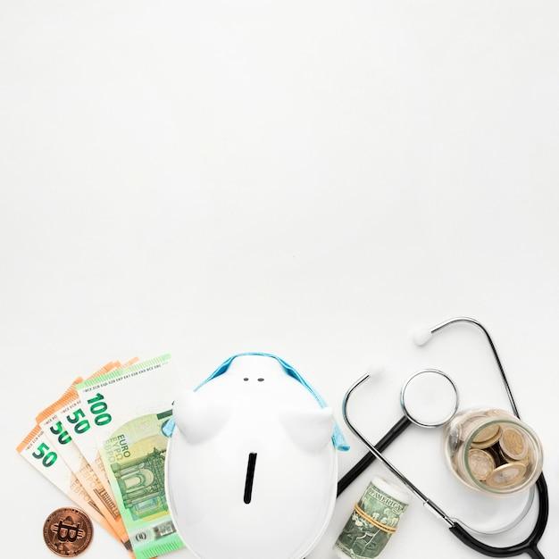 Bovenaanzicht spaarvarken met geld en stethoscoop Gratis Foto
