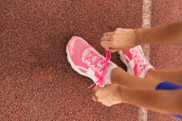 Bovenaanzicht sportieve vrouw bindt schoenen veters Gratis Foto