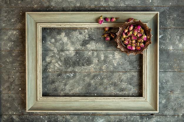 Bovenaanzicht steeg thee in kom en een houten leeg frame Gratis Foto