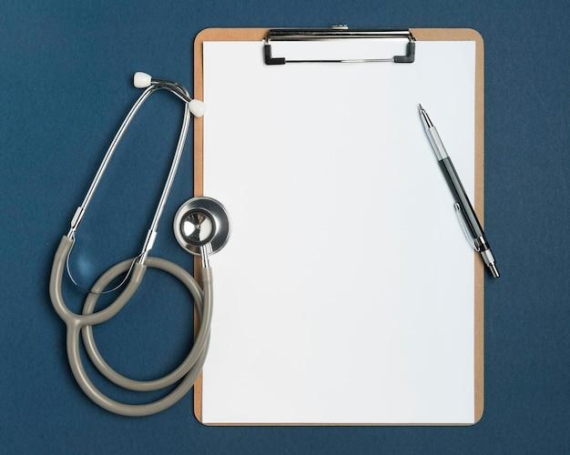 Bovenaanzicht stethoscoop met klembord en pen Gratis Foto