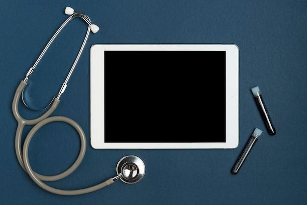 Bovenaanzicht stethoscoop met tablet en bloedmonsters Gratis Foto