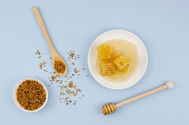 Bovenaanzicht stuifmeel met honingraten en lepel Gratis Foto