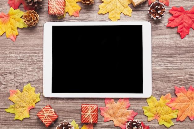 Bovenaanzicht tablet versierd met kleurrijke esdoorn bladeren op houten oppervlak Premium Foto