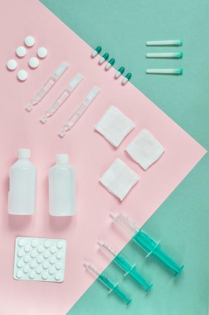 Bovenaanzicht tabletten, spuiten m verschillende medische op gekleurd karton, roze, blauw en lichtgroen. medicijnen op kleurkarton op een rij. bovenaanzicht. flatlay. indeling Premium Foto