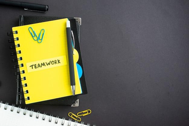 Bovenaanzicht teamwerk notitie met blocnotes op donkere achtergrond Gratis Foto
