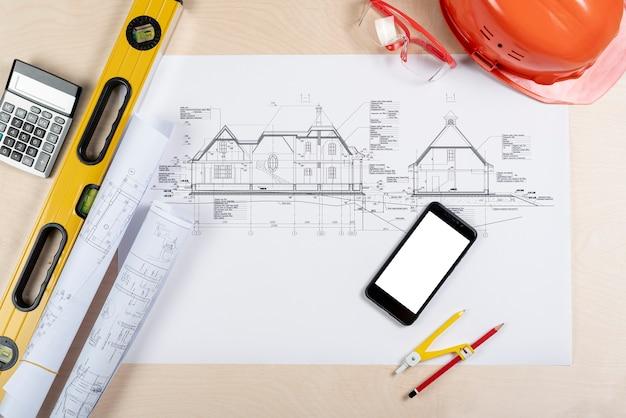 Bovenaanzicht telefoon bovenop architecturale plannen mock-up Gratis Foto