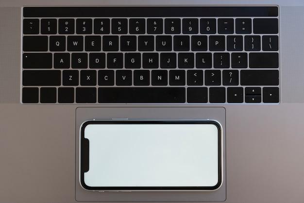 Bovenaanzicht telefoon op laptop touchpad Gratis Foto