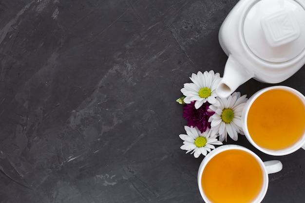 Bovenaanzicht thee kopjes en bloemen met kopie ruimte Gratis Foto