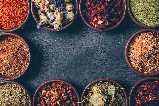 Bovenaanzicht thee kruiden in kommen op donkere gestructureerde achtergrond. horizontale ruimte voor tekst Gratis Foto
