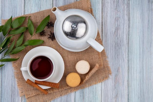 Bovenaanzicht theepot met een kopje thee kaneel en bitterkoekjes op een beige servet op een grijze tafel Gratis Foto