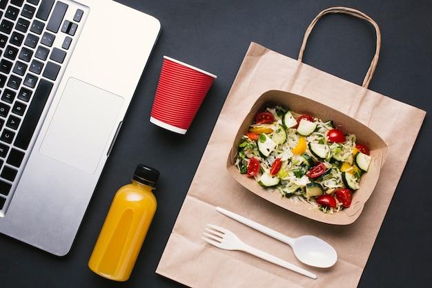 Bovenaanzicht toetsenbord en salade op zwarte achtergrond Gratis Foto