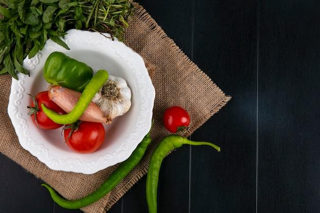 Bovenaanzicht tomaten met bulgaarse knoflook en hete pepers en uien in een plaat met munt op een beige servet Gratis Foto