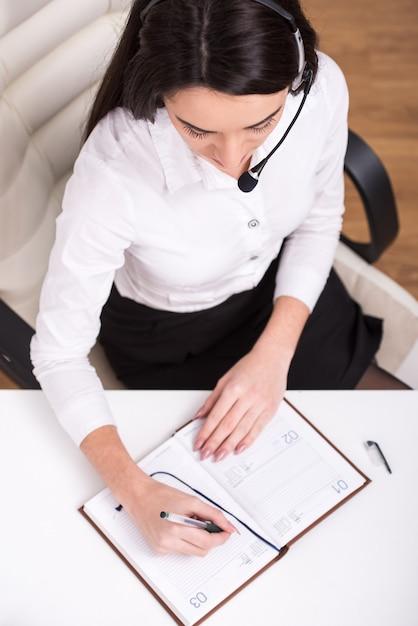 Bovenaanzicht van aantrekkelijke vrouw werkt in een callcenter. Premium Foto
