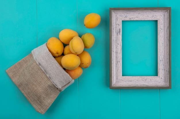 Bovenaanzicht van abrikozen in een jutezak met een grijs frame op een blauw oppervlak Gratis Foto
