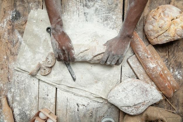 Bovenaanzicht van afro-amerikaanse man kookt vers ontbijtgranen, brood, zemelen op houten tafel. lekker eten, voeding, ambachtelijk product. glutenvrij eten, gezonde levensstijl, biologische en veilige productie. handgemaakt. Gratis Foto