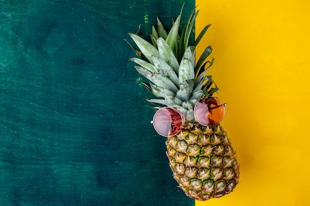 Bovenaanzicht van ananas met rode bril Gratis Foto