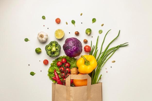 Bovenaanzicht van assortiment van groenten in papieren zak Gratis Foto