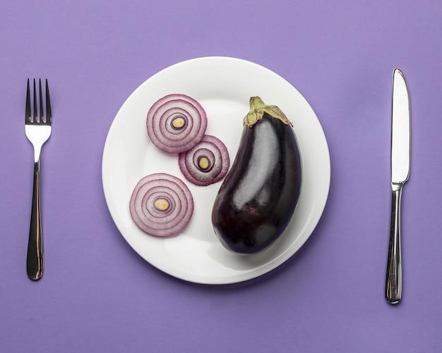 Bovenaanzicht van aubergine en ui op plaat met bestek Gratis Foto