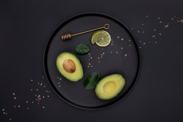 Bovenaanzicht van avocado en limoen op plaat Gratis Foto