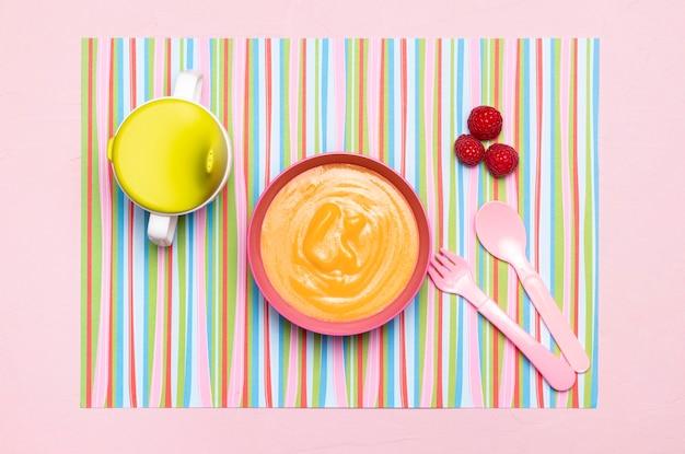Bovenaanzicht van babyvoeding in kom met bestek en fruit Gratis Foto