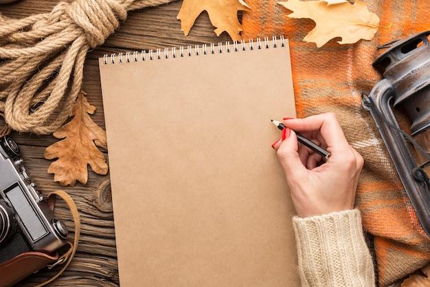 Bovenaanzicht van bladeren met notebook en camera Gratis Foto