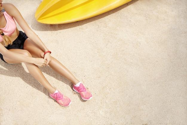Bovenaanzicht van blanke vrouw loper in sportkleding zittend op het strand na actieve training aan zee. sportvrouw in roze loopschoenen die haar adem vangen terwijl het rusten op zand tijdens training Gratis Foto