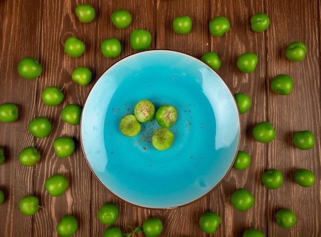 Bovenaanzicht van blauw bord met gesneden groene pruimen bestrooid met gedroogde pepermunt en zure groene pruimen gerangschikt rond op houten tafel Gratis Foto