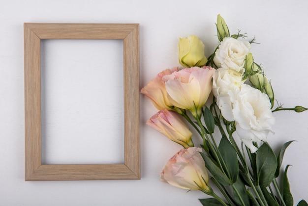 Bovenaanzicht van bloemen en frame op witte achtergrond met kopie ruimte Gratis Foto